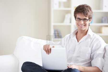 Photo for Smiling man with laptop at home - Royalty Free Image