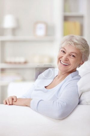 Photo for Smiling elderly woman at home on the couch - Royalty Free Image
