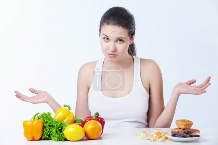 Photo for Doubting the girl with a healthy diet and sweet on a white background - Royalty Free Image