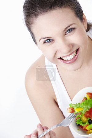 Photo for Attractive young girl eating salad on a white background - Royalty Free Image
