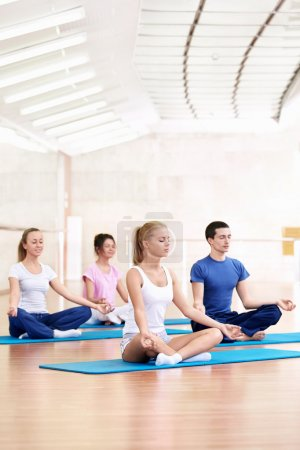 Photo for Young practice yoga in the fitness club - Royalty Free Image