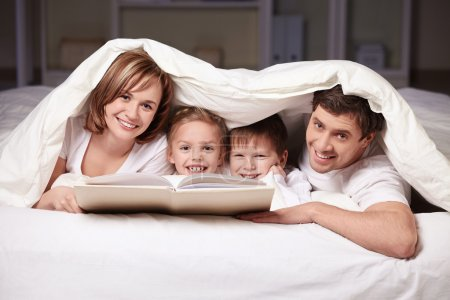 Photo for Parents and children with a book under a blanket - Royalty Free Image
