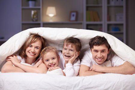 Photo for Families with children in bed under a blanket - Royalty Free Image