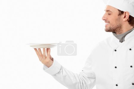 Photo for A smiling cook looks at the empty plate on a white background - Royalty Free Image