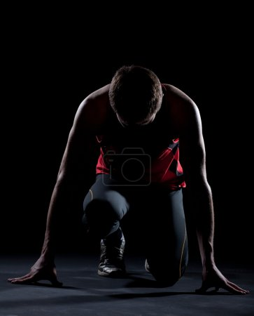 Photo for Athlete ready to start on black background - Royalty Free Image