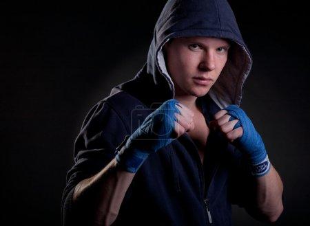 Photo pour Jeune homme dans une hotte sur fond noir - image libre de droit