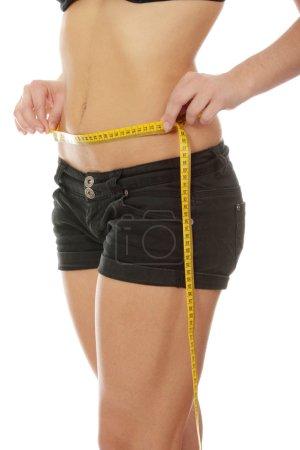 Photo pour Sexy, en forme, jeune femme mesurant sa taille, isolée sur blanc - image libre de droit