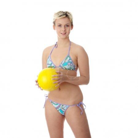 Teen woman in bikini playing volleyball