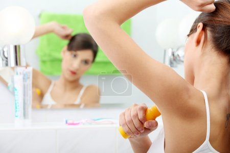 Young beautiful caucasian woman using deodorant
