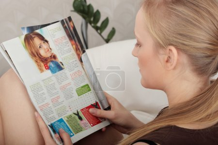 Young woman reading a magazine