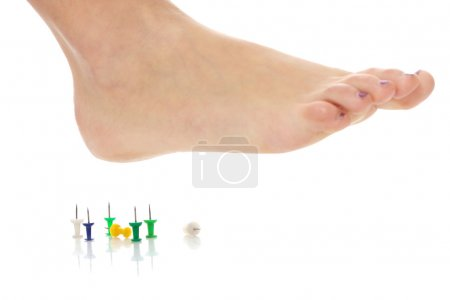 Photo for Female foot above pushpin, isolated on white background - Royalty Free Image