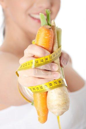 Photo pour Main de femme tenant des légumes et mètre ruban, isolé sur blanc. notion de régime - image libre de droit
