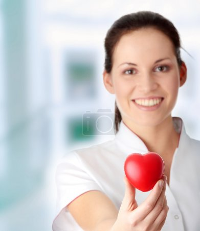Photo for Young nurse with heart in her hand - Royalty Free Image
