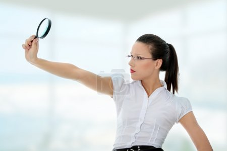 Photo for Young attractive business woman looking into a magnifying glass - Royalty Free Image