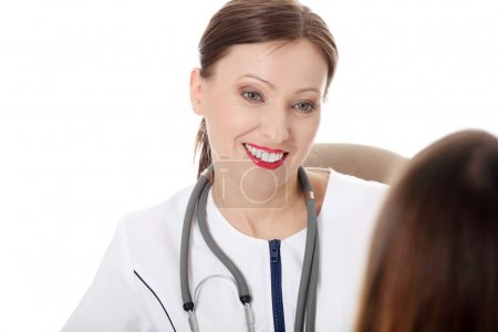 Mature smiling female doctor with female patient.