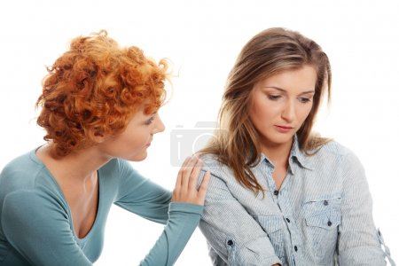 Troubled young girl comforted by her friend
