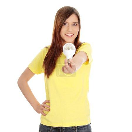 Photo pour Jeune femme heureuse, tenant l'ampoule diode, isolé sur blanc - image libre de droit