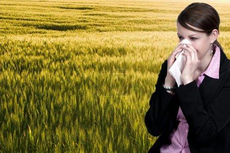 Photo pour Une belle femme avec un rhume, un rhume des foins ou des allergies qui se mouchent - image libre de droit