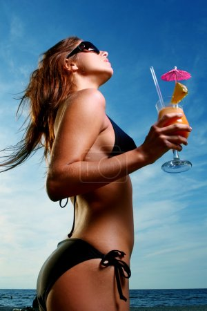 Photo for Young and attractive lady drink fresh summer fruit cocktail on a beach - Royalty Free Image