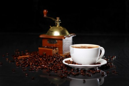 Photo for Coffee mill and cup on the table with coffee beans around - Royalty Free Image