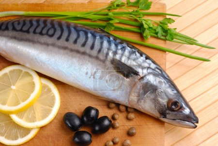 Fresh mackerel with olives, lemons and onions on t...