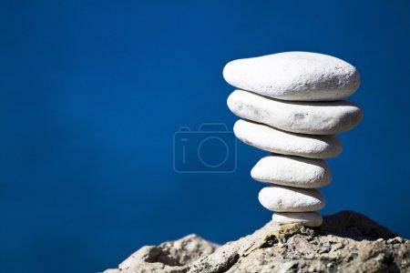 Photo pour Gros plan de la pile blanche de pierres sur la mer bleue - image libre de droit