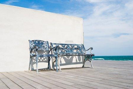 Photo pour Banc sur sol en bois avec mur blanc dans la plage . - image libre de droit