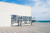Bench on wooden floor in the beach.