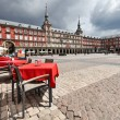 Cafe tables with red tableclothes in Plaza Mayor. ...