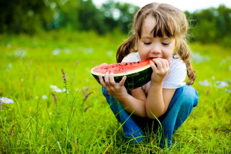 Photo for Cute little girl eating watermelon on the grass in summertime - Royalty Free Image