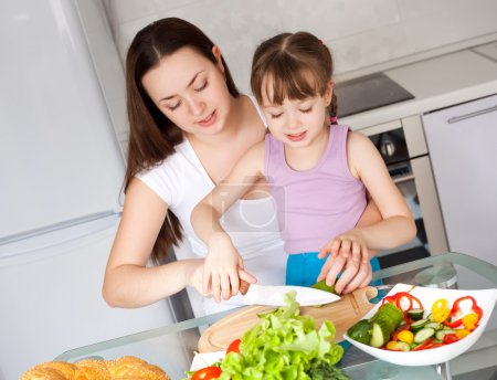 Photo for Young mother and her five year old daughter cook together on the kitchen at home - Royalty Free Image