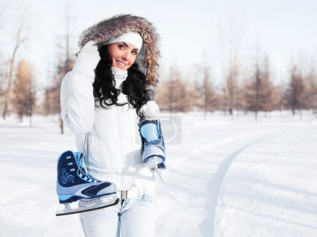 Photo for Beautiful brunette girl wearing warm winter clothes going to ice skate - Royalty Free Image