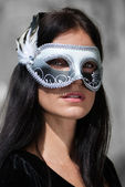 Portrait beautiful woman in black dress wearing carnival mask