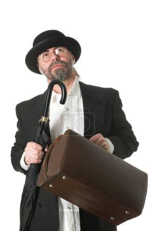Photo pour Voyager homme d'affaires d'âge moyen dans un costume d'affaires et un parapluie et sac de voyage dans ses mains . - image libre de droit
