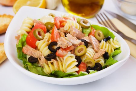 Photo for Classic tuna salad with pasta, olives and tomato - Royalty Free Image