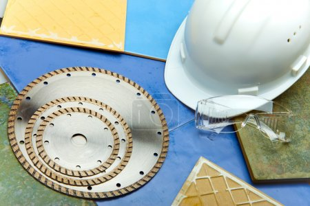 Diamond discs for cutting of tile, goggles and a helmet on a tile