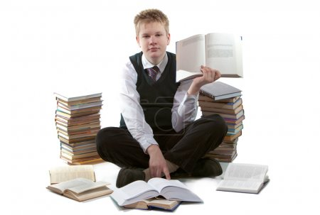 The schoolboy in a school uniform sits on a floor, near to packs of books,