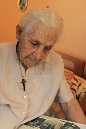 Foto de Mujer Senior, 92 años, buscando fotos de un álbum - Imagen libre de derechos