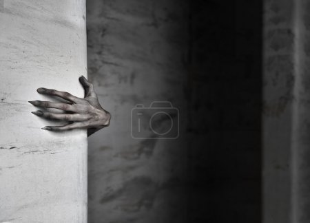 Photo for A spooky female hand protruding from behind a wall - Royalty Free Image