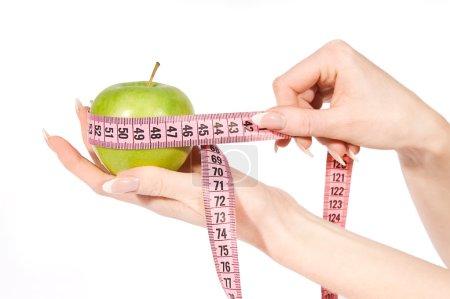 Woman hands measuring green apple