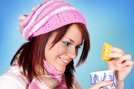 Photo for Cute winter girl adding lemon to her tea - Royalty Free Image