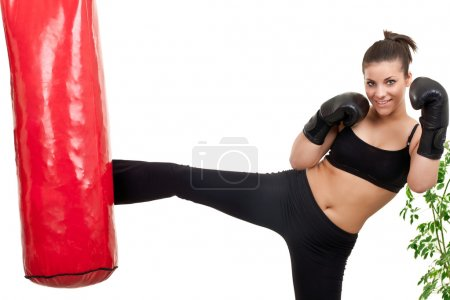 Photo for Female boxer kicking punching bag at home - Royalty Free Image