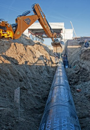 Photo pour Excavatrice définie des tuyaux en acier dans une tranchée - image libre de droit