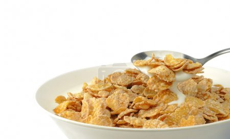 Photo pour Gros plan d'une cuillère dans un bol avec des flocons de maïs et du yaourt . - image libre de droit