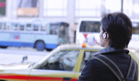Man with headphones in a city at the traffic light.