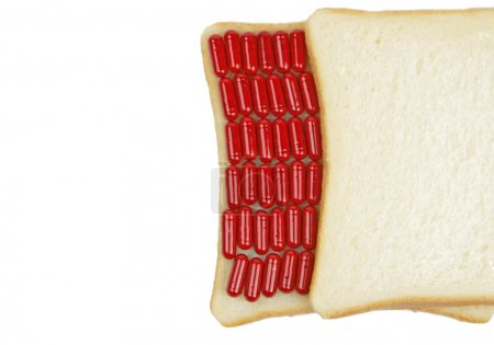 Photo for Abstract image of some red capsules between two slices of bread.Useful in design suggesting to drugs abuse concepts. - Royalty Free Image