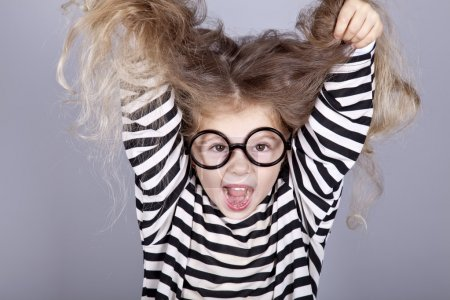 Young shouting child in glasses and striped knitted jacket.