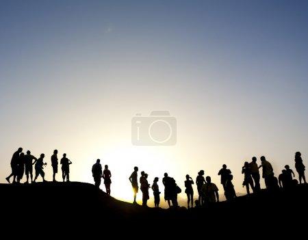 Groupe de silhouette contre le soleil au sommet d'une montagne