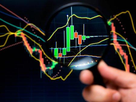 Photo pour Loupe et graphique, outils de base de l'analyse technique sur le marché boursier . - image libre de droit