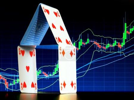Photo pour Château de cartes avec un graphique de stock dans les thèmes d'hypothèque représentent fond... - image libre de droit